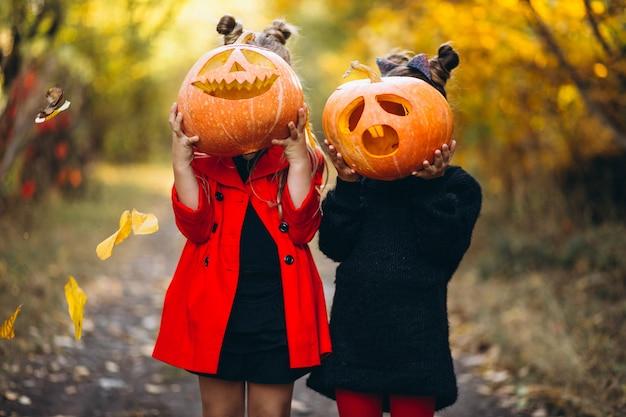 De kinderenmeisjes kleedden zich in openlucht in halloween-kostuums met pompoenen