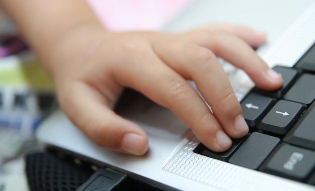 De kinderhand houdt een computermuis of -toetsenbord vast. kind leert online en speelt thuis een spel op de computer. school, onderwijs, spel en technologie concept.