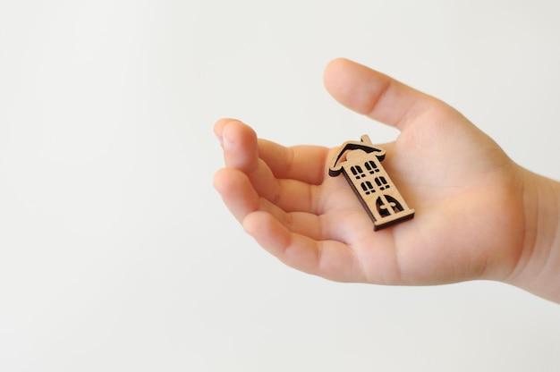 De kinderhand houdt een speeltje vast in de vorm van een houten huis