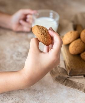 De kinderhand pakt havermoutkoekjes van het bord gezonde snack of dessert selectieve focus