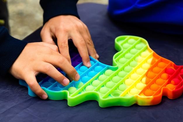 De kinderhanden drukken op de veelkleurige pop het close-up