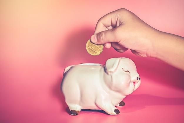 De kindhand laat vallen een muntstuk in spaarvarken om te bewaren
