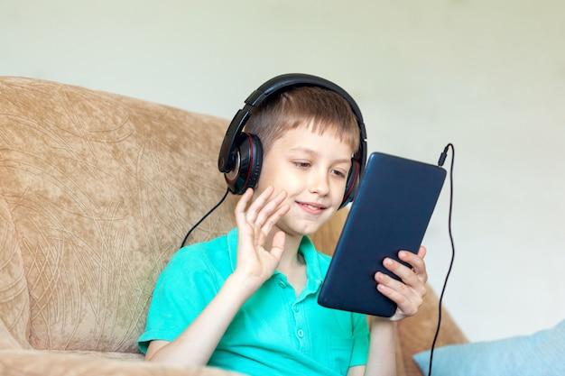De kindjongen die digitale tablet gebruiken en telefoneert.