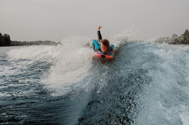 De kindjongen kleedde zich in zwempak surfen liggend op oranje raad