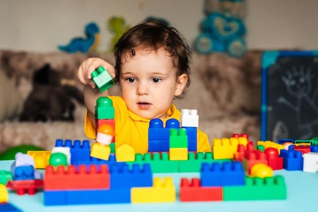 De kindjongen leert om een huis van blokken te bouwen