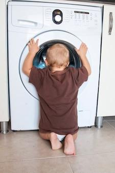 De kindjongen onderzoekt de wasmachine