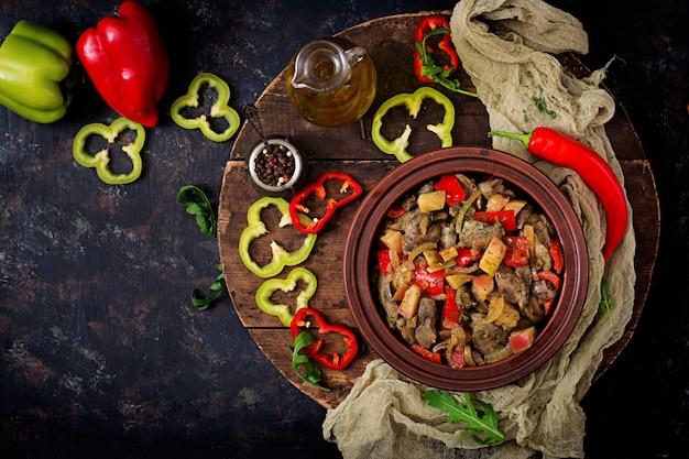 De kippenlever van het braadstuk met groenten op houten achtergrond. plat leggen. bovenaanzicht