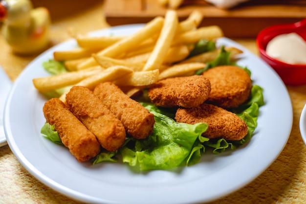 De kippenstokken van de zijaanzicht met goudklompjes en frieten op slablad