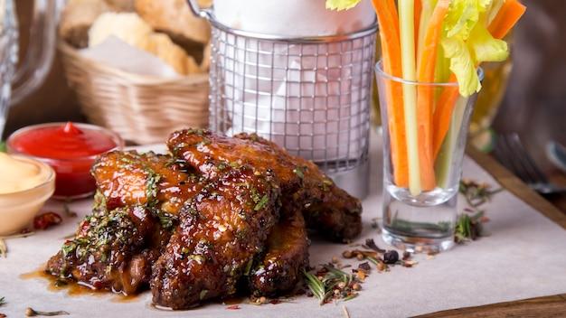 De kippenvleugels van de barbecue op houten dienblad met frieten en groenten. detailopname