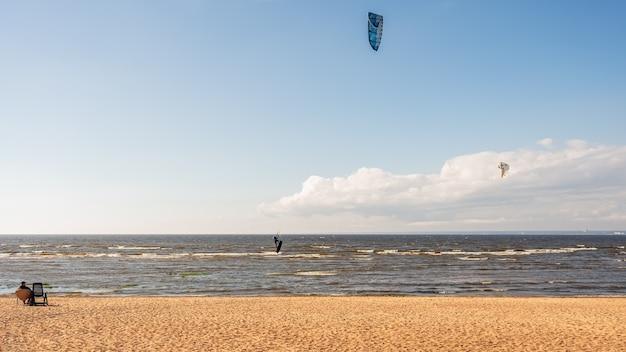 De kitesurfer rijdt op de golven van de baai