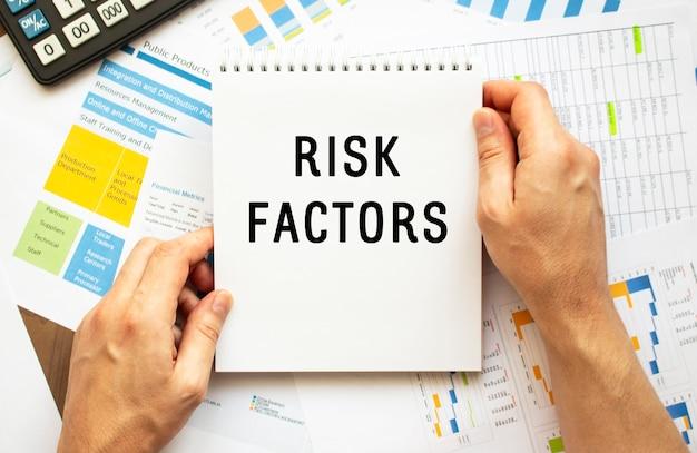 De kladblok van de zakenmangreep met tekst risicofactoren. financiële grafieken op de desktop