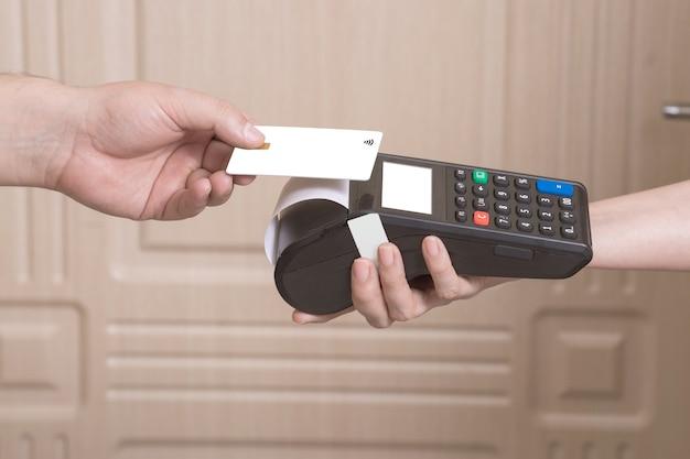 De klant betaalt de koerier voor thuisbezorging contactloos met een creditcard via smartphone