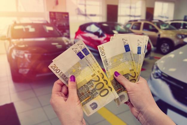 De klant betaalt eurobankbiljetten voor zijn droom - een nieuwe auto.