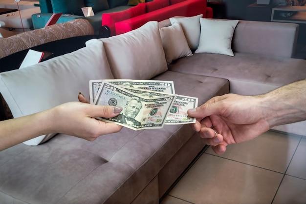 De klant koopt nieuwe meubels in de winkel, geeft dollars aan de verkoper.