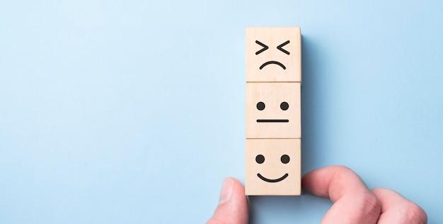 De klanten kozen met de hand het happy face smile face-pictogram en het vijfsterrensymbool op een houten kubus op tafel
