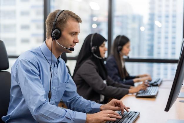 De klantenserviceagent van de exploitant met hoofdtelefoons die aan computer in een call centre werken