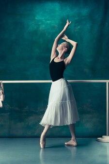 De klassieke balletdanser in witte tutu poseren bij ballet barre op studio achtergrond