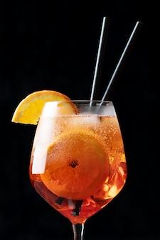 De klassieke italiaanse aperol spritz cocktail in glas op zwarte, sluit omhoog