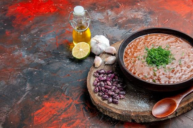 De klassieke lepel van het de bonenknoflook van de tomatenzeep op houten scherpe raad en de citroen van de oliefles