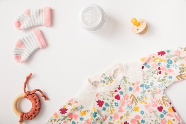 De kleding en de sokken van de baby met fopspeen en stuk speelgoed op witte achtergrond worden geïsoleerd die