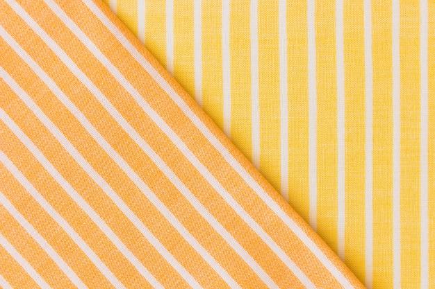 De kledingachtergrond van geel en een oranje stof