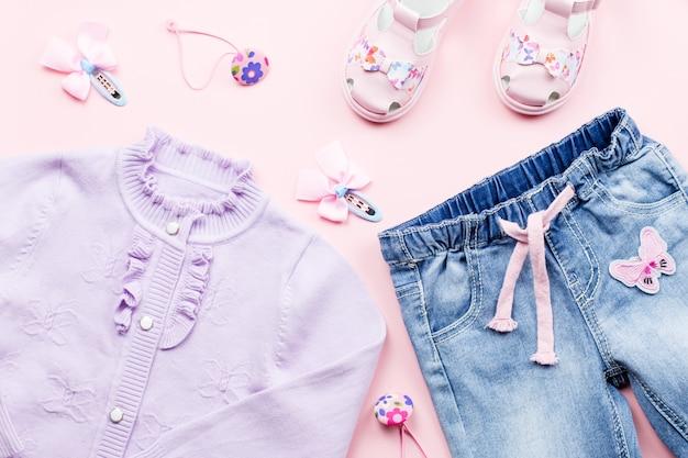 De kledingcollectie van het kleine meisje plat lag met vest, jeans, sandalen op roze.