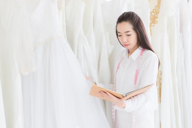 De kleermaker die de boetiek bezit, controleert het aantal trouwjurken in de winkel.