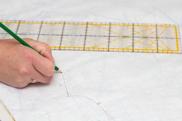 De kleermaker die een sjabloon maakt. de hand van de naaister met een potlood op het patroon en een liniaal. werk op maat.