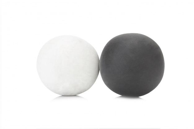 De klei enige zwarte en witte bal van de plasticine op witte close-up als achtergrond