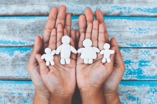 De klei gelukkige familie van de plasticine op kind en ouderhanden