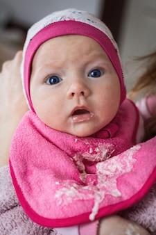 De kleine baby brak uit met moedermelk