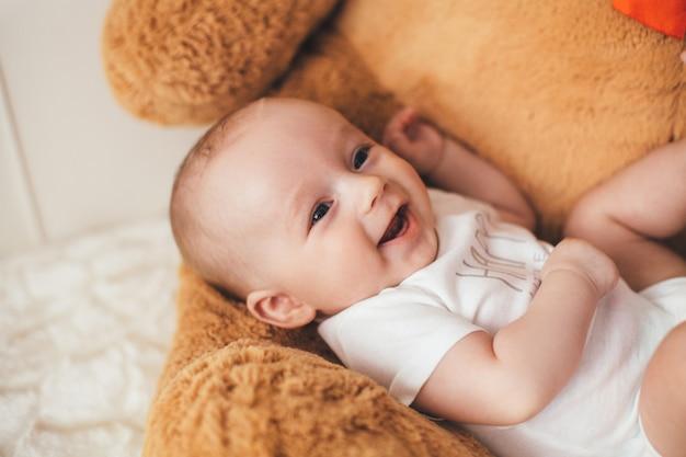 De kleine baby ligt op de beer