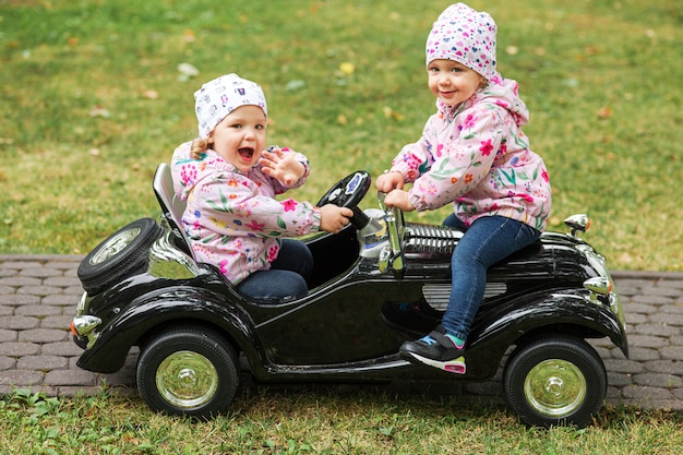 De kleine baby meisjes spelen met een auto