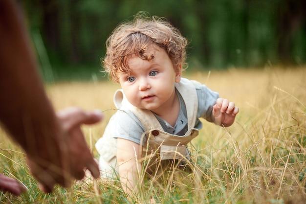 De kleine baby of jaar oude kind op het gras in zonnige zomerdag