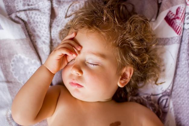 De kleine baby slaapt en wordt wakker