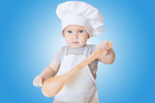 De kleine babyjongen in een pak van de kok beeldhouwt deeg kleine kinderscullion maakt diner in kokskostuum