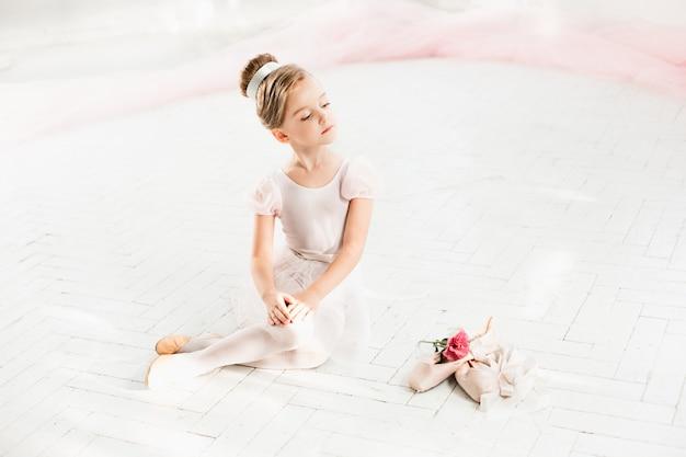 De kleine balerina in witte tutu in de klas op de balletschool