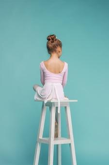 De kleine balerinadanser op blauwe muur