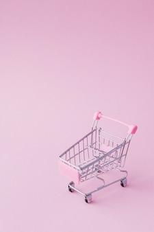 De kleine de duwkar van de supermarktkruidenierswinkel voor het winkelen stuk speelgoed met wielen en roze plastic elementen op roze pastelkleurdocument vlakte legt achtergrond. concept van winkelen. ruimte voor reclame kopiëren