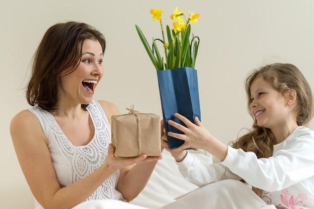 De kleine dochter houdt een geschenk en bloemen