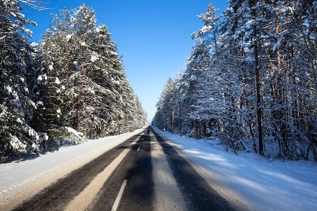De kleine geasfalteerde weg naar een winterseizoen. wit-rusland