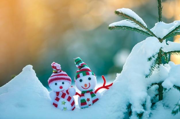 De kleine grappige sneeuwman van de speelgoedbaby in gebreide mutsen en sjaals in diepe sneeuw