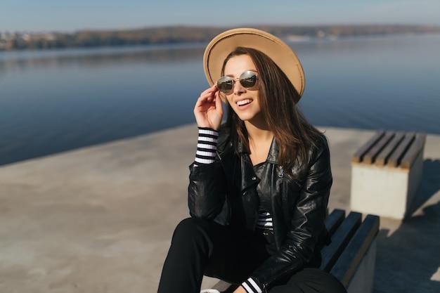 De kleine jonge modelvrouw van het meisje zit op een bank in de herfstdag aan de waterkant van het meer, gekleed in vrijetijdskleding
