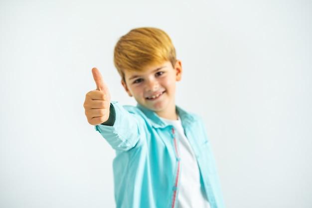 De kleine jongen duimen omhoog op de witte achtergrond