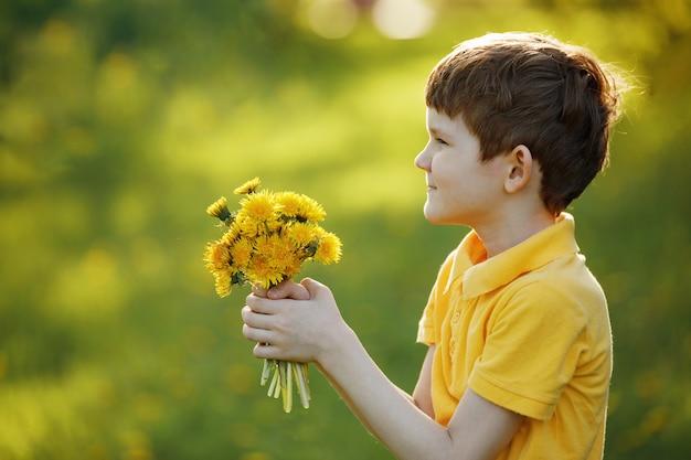 De kleine jongen geeft een boeket gele paardebloemen aan zijn moeder of meisjesvriend.