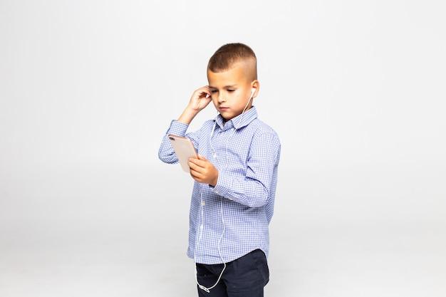 De kleine jongen in hoofdtelefoons luistert muziek die op witte muur wordt geïsoleerd