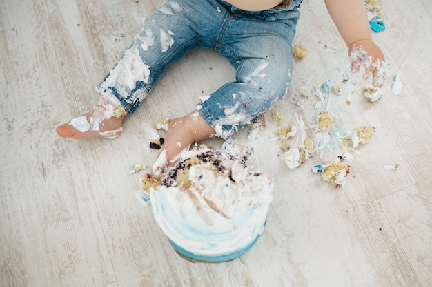 De kleine jongen is allemaal betrapt met een taart