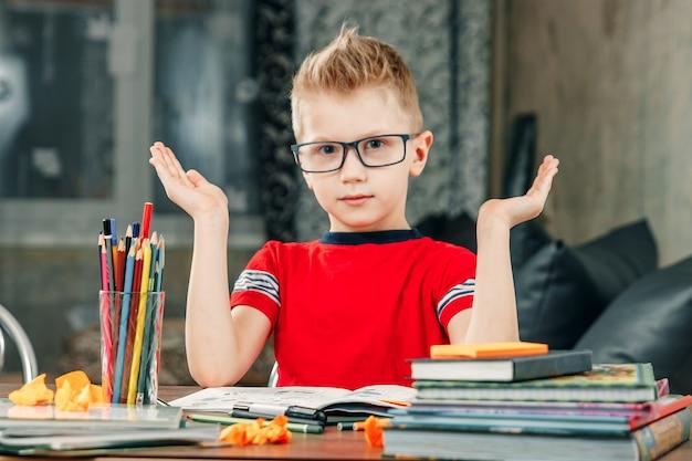 De kleine jongen is verdrietig, verveeld om huiswerk te maken.