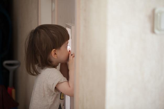 De kleine jongen kijkt in het raam van de deur.