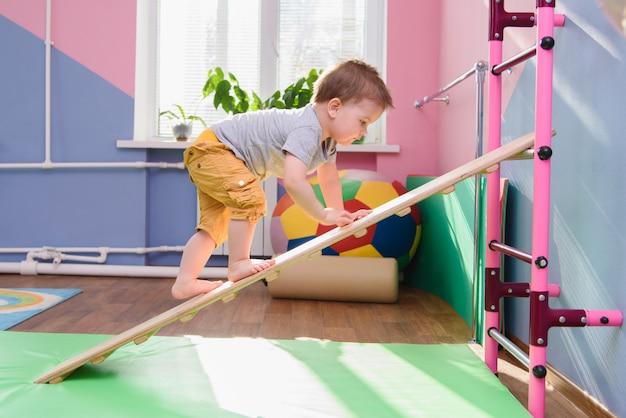 De kleine jongen klimt op een houten bord in de sportschool